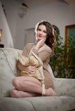 Jeune femme sensuelle s'asseyant sur la détente de sofa Belle longue fille de cheveux avec les vêtements confortables rêvassant s Image stock