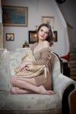 Jeune femme sensuelle s'asseyant sur la détente de sofa Belle longue fille de cheveux avec les vêtements confortables rêvassant s Photo stock
