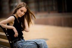 Jeune femme sensuelle touchant ses cheveux tout en se reposant sur le banc Photographie stock libre de droits