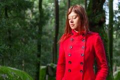 Jeune femme sentant seule la marche triste sur le chemin forestier portant le long manteau rouge Photo stock