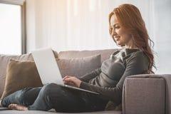 Jeune femme sereine à l'aide de son ordinateur portable à la maison Image libre de droits