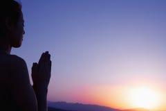 Jeune femme sereine avec des mains ensemble dans la pose de prière dans le désert en Chine, silhouette, arrangement du soleil Image libre de droits