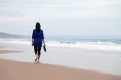 Jeune femme seul marchant loin dans une plage abandonnée photo libre de droits