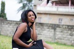 Jeune femme seul s'asseyant dans un jardin photos stock