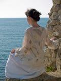 Jeune femme seul sur la pierre regardant à la mer Images stock
