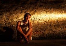 Jeune femme seule s'asseyant sur la rue Images libres de droits