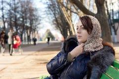 Jeune femme seule s'asseyant sur un banc de parc Images libres de droits