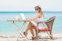 Jeune femme sexy à l'aide de l'ordinateur portable sur la plage Travaillent en indépendants le travail Photo stock