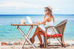 Jeune femme sexy à l'aide de l'ordinateur portable sur la plage Travaillent en indépendants le travail Image libre de droits