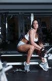 Jeune femme sexy après séance d'entraînement dans le gymnase Photo stock