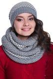 Jeune femme sexy assez gaie utilisant le chandail, l'écharpe et le chapeau tricotés D'isolement sur le fond blanc Elle sourit photographie stock