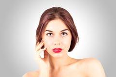 Jeune femme sexy avec de belles lèvres rouges regardant l'appareil-photo sur le fond gris Femme de beauté avec les lèvres rouges  Photos stock