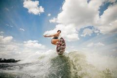 Jeune femme sexy ayant l'anf wakesurfing d'amusement sautant sur le conseil images stock