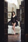 Jeune femme sexy dans la lingerie posant sur sa chambre à coucher Photographie stock libre de droits