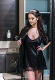 Jeune femme sexy dans la lingerie utilisant le corps noir et le neglige Photographie stock libre de droits