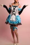 Jeune femme sexy dans la robe érotique Alice au pays des merveilles sur un fond rose Image stock