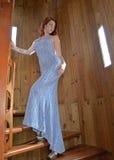 Jeune femme sexy dans la robe de soirée bleue marchant vers le haut de l'escalier en spirale Images stock