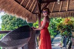 Jeune femme sexy dans la robe rouge dans un café tropical sur le fond de l'palmiers et plantes tropicales Bali, Indonésie Image libre de droits