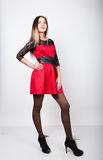 Jeune femme sexy de beauté dans la robe rouge avec des douilles de dentelle dans la pose de talons hauts Photo libre de droits