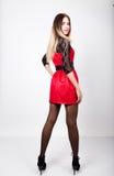 Jeune femme sexy de beauté dans la robe rouge avec des douilles de dentelle dans la pose de talons hauts Photos stock