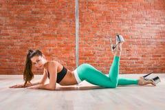 Jeune femme sexy de danse de poteau posant contre le mur de briques Image stock