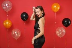 Jeune femme sexy de tentation dans peu de robe noire célébrant sur les ballons à air rouges lumineux de fond ` S de St Valentine photo stock