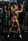 Jeune femme sexy et musculaire dans les sous-vêtements posant contre le gymnase, plein chiffre de corps Photos libres de droits