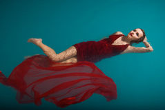 Jeune femme sexy flottant sur la piscine en rouge Photo stock