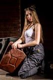 Jeune femme sexy impulsive habillée comme mécanicien automobile et verres de soudure tenant la boîte métallique de carburant images libres de droits