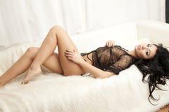 Jeune femme sexy mince dans la lingerie sur la fourrure blanche Photographie stock libre de droits
