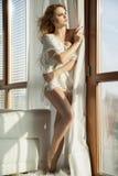 Jeune femme sexy mince dans le chandail blanc contre la fenêtre Photo libre de droits