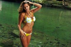 Jeune femme sexy posant dans le bikini de concepteur à l'emplacement exotique de la rivière de montagne images libres de droits