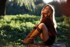 Jeune femme sexy s'asseyant sur le log photo stock