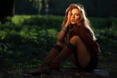 Jeune femme sexy s'asseyant sur le log photographie stock