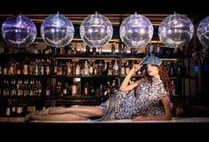 Jeune femme sexy se trouvant sur la barre à un club de disco de nuit Images stock