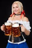 Jeune femme sexy utilisant un dirndl avec deux tasses de bière sur le fond noir Images stock