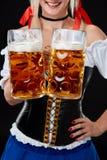 Jeune femme sexy utilisant un dirndl avec deux tasses de bière sur le fond noir Photos libres de droits