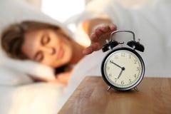 Jeune femme somnolente étirant la main au tour disposé de sonnerie d'alarme il  Réveillez-vous tôt, en n'obtenant pas assez de do image libre de droits