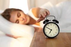 Jeune femme somnolente étirant la main au tour disposé de sonnerie d'alarme il  Réveillez-vous tôt, en n'obtenant pas assez de do image stock