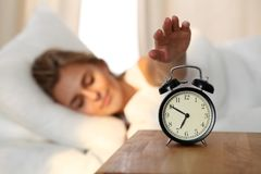 Jeune femme somnolente étirant la main au tour disposé de sonnerie d'alarme il  Réveillez-vous tôt, en n'obtenant pas assez de do images libres de droits