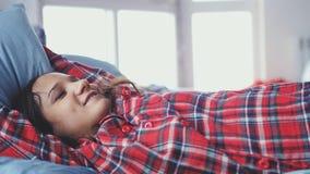Jeune femme somnolente dans des pyjamas se situant dans le lit réveillant l'étirage et souriant pendant le matin Image libre de droits