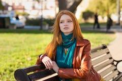 Jeune femme songeuse attirante s'asseyant sur le banc en parc photo stock