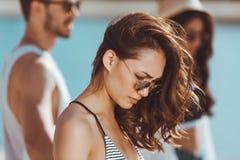 Jeune femme songeuse dans des lunettes de soleil regardant vers le bas tout en se tenant sur la plage Photo stock