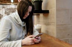 Jeune femme songeuse de brune dans une chemise lumineuse utilisant l'Internet dans son téléphone portable se reposant en café photo libre de droits