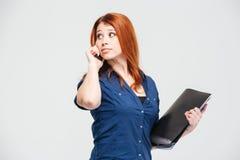 Jeune femme songeuse de sourire avec le dossier parlant au téléphone portable Photos stock