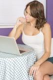 Jeune femme songeuse réfléchie attirante à l'aide de l'ordinateur portable Photographie stock