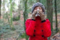 Jeune femme souffrant d'un froid ou d'une grippe soufflant son nez Photos stock
