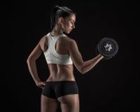 Jeune femme soulevant les haltères Photo stock