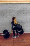 Jeune femme soulevant les poids lourds au gymnase Photographie stock