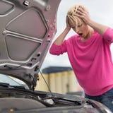 Jeune femme soumise à une contrainte avec le défaut de voiture Image libre de droits